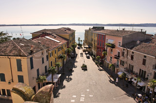 Aerial view on paved street among vintage houses and Lake Garda in Sirmione, northern Italy