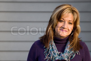 A pretty middle aged woman with a very sincere smile