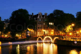 View on city canal (Amstel river) and small illuminated bridge at evening in Amsterdam, Netherlands (Holland)