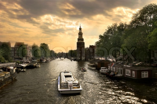 View on city canal (Amstel river) with cruise ship in Amsterdam, Netherlands