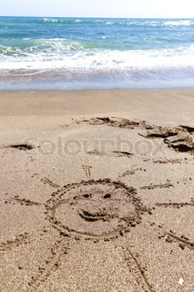 On a sandy beach, a sun drawn in the sand