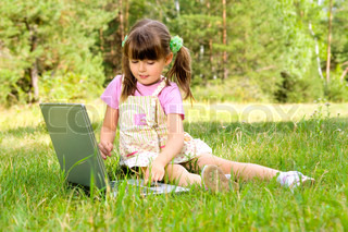 The small nice girl works on a computer, sits on a beautiful green lawn, Smile  Profile Adobe RGB (1998)