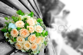 The beautiful wedding bouquet flowers lays on a bench, on a background a newly-married couple sit Focus on a bouquet gray and color