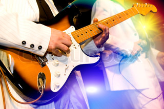 The guitar-player plays an electroguitar, the second person with a microphone on a background, bright multi-coloured light