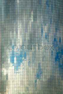 Glass wall of business center with sky reflection