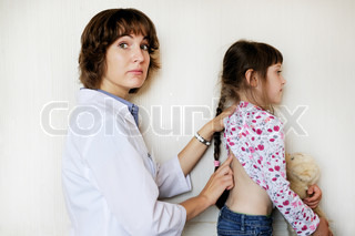 Young female doctor examines a little child girl on a white background
