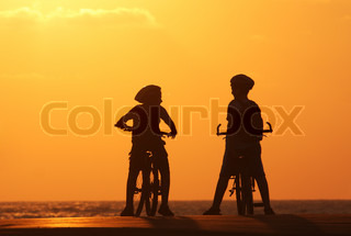 Silhouette of two kids on bicycles standing on the pear on Mediterranean Sea at sunset