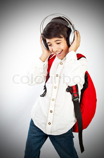 Pretty teen boy enjoying music, holding head with headphones, expressing pleasure and having fun, singing a song