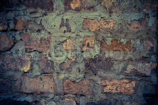 Very old brick wall covered with brown patina