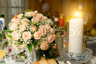 the Candles and wedding bouquet roses on a banquet table, beautifully