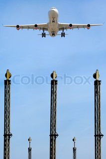 A plane is flying over the landing lights in an airport
