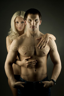 muscular handsome sexy guy with pretty woman on dark background