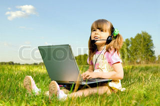 The small nice girl works on a computer, sit on a beautiful green lawn, Smile