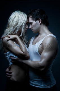 muscular handsome sexy guy with pretty woman, on dark background, glamour blue light