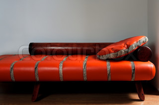Leather red sofa on a background of a wall