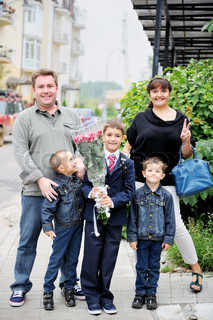 Happy young family with three sons accompanies the eldest son to school
