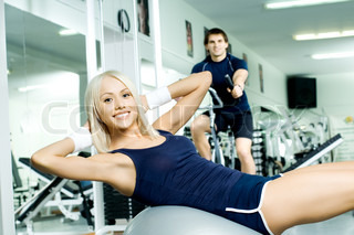 happy cutie athletic girl ,  execute exercise on muscles belly  and smile, in  sport-hall