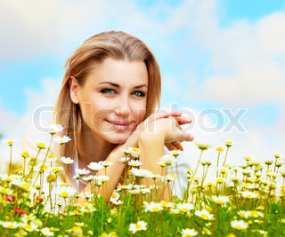 Young beautiful girl laying on the daisy flowers field, outdoor portrait, summer fun concept