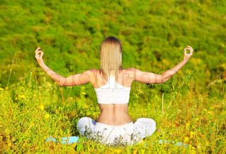 Healthy female doing yoga outdoor, sitting in lotus posture, body care and inner peace concept