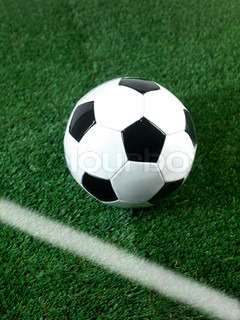 Black and white soccer balls isolated on artificial grass