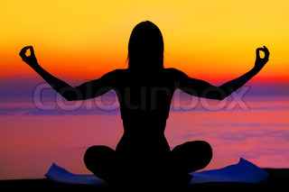 Healthy woman doing yoga outdoor, sunset over sea, body care & meditation concept