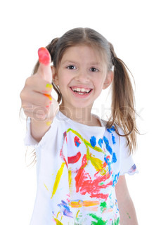 Happy little girl in a paint shows a thumb upwards