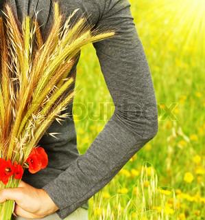 Wheat bouquet in girls hand, harvest concept