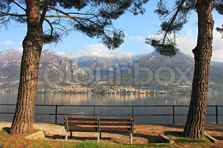 Bench between two trees on the promenade along the mountains and Lake Como in Italy