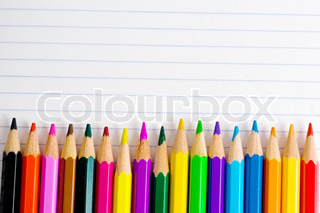 Row of color pencils on a blank lined notebook sheet