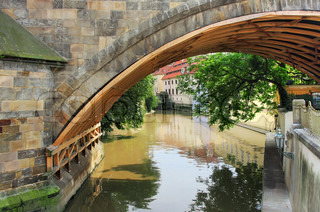 View on city canal from under the Charles Bridge in Prague