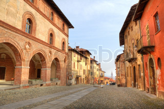 Paved street among old historic houses in town of Saluzzo, northern Italy