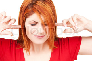 picture of unhappy redhead woman with fingers in ears