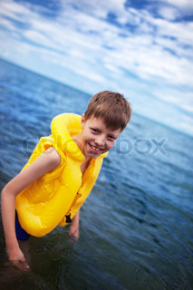 Smiling boy in the life-vest in the water