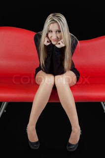 Beautiful girl sitting on red couch,on black background
