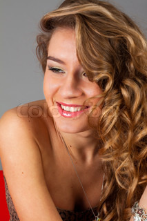 attractive naked girl smiling in studio on gray background
