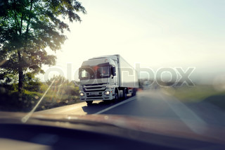 European truck speeding on freeway with colorful ambiental colours and blurred motion