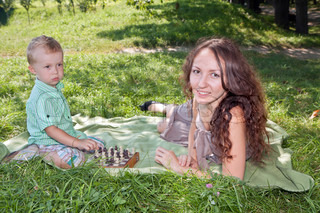 Mother teaches her son to play chess in the park