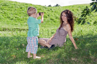 Son photographing his beautiful mother in the park a mobile phone