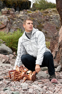 man with crab and sea urchin on rocky shore