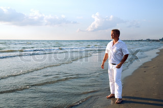 man in white clothing at sea beach