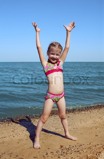 girl child at the sea hands up