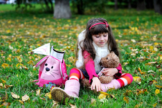 Adorable little brunette girl in pink outfit sitting on a grass