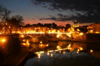 View on Tiber river and night illuminated Vatican city at evening from Saint Angel Bridge in Rome, Italy