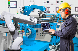 Engineer using laptop computer for maintenance automatic robotic hand machine tool at industrial manufacture factory