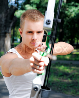 young man with a bow and arrows in the woods