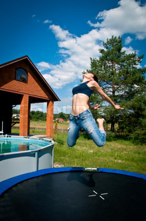 beautiful brunette high jumps on a trampoline