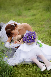 Happy wedding couple kissing on fresh green grass