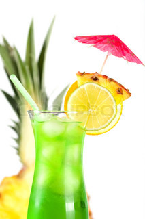 Green tropical cocktail with pineapple, orange and lime slices on white background