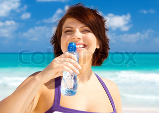 happy woman with bottle of water on the beach