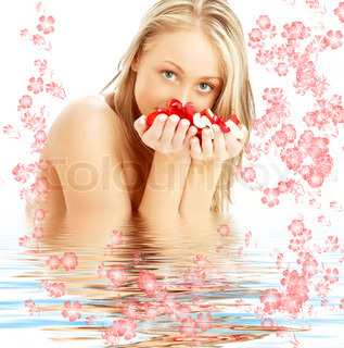 lovely blond with red and white rose petals and flowers in water